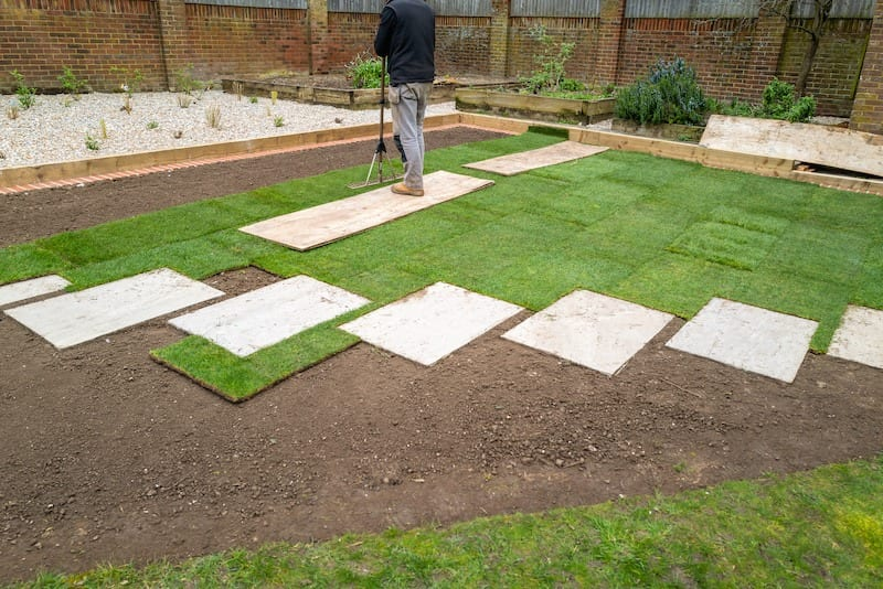 New turf installation within an area with new slab stepping stones, in a newly landscaped garden.
